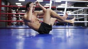 Muskulösa drev för en man i den oxing idrottshallen som gör sit up för mage med de svettiga musklerna som dras och Ung boxare stock video