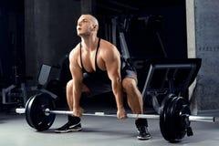 Muskulösa män som lyfter Deadlift i idrottshallen Arkivbilder