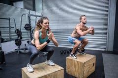 Muskulösa par som gör banhoppningsquats royaltyfria bilder
