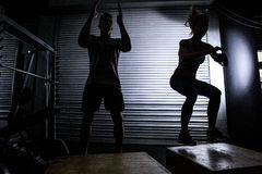 Muskulösa par som gör banhoppningsquats royaltyfri bild