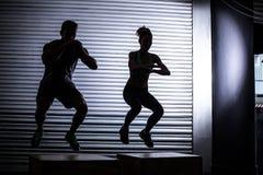 Muskulösa par som gör banhoppningsquats fotografering för bildbyråer