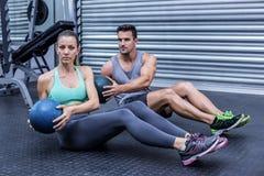 Muskulösa par som gör buk- bollövning royaltyfri foto