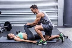 Muskulösa par som gör en bensträckning arkivfoto