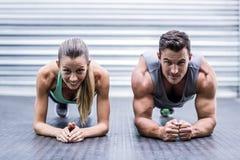 Muskulösa par som gör plankövningar royaltyfri foto
