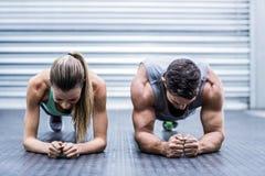 Muskulösa par som gör plankövningar arkivfoton