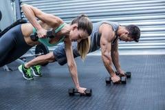 Muskulösa par som gör plankan, övar tillsammans Fotografering för Bildbyråer
