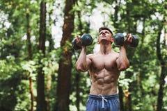 Muskulöse anhebende Gewichte des jungen Mannes im Park stockbild