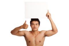 Muskulöse asiatische Manndaumen oben mit leerem Zeichen Lizenzfreies Stockfoto