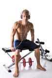 Muskulöse blonde anhebende Gewichte des jungen Mannes und Hören Musik in den Kopfhörern Lizenzfreie Stockfotografie