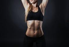 Muskulöse Eignungsfrau, die auf einem dunklen Hintergrund im Studio aufwirft Stockbild