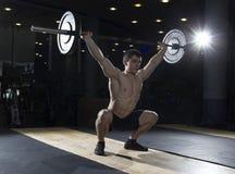 Muskulöse Eignungsmann deadlifts ein Barbell über seinem Kopf im GY lizenzfreie stockbilder