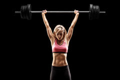 Muskulöse Frau, die einen schweren Barbell anhebt Lizenzfreies Stockbild