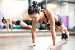 Muskulöse Frau, die Planken-Übung im Eignungs-Studio tut stockfotografie