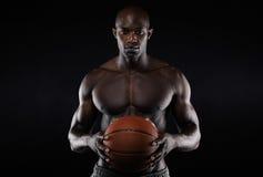 Muskulöse hemdlose Holding des jungen Mannes ein Basketball Lizenzfreie Stockbilder