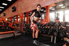 Muskulöse junge Frau mit dem schönen Körper, der Übungen mit Dummkopf tut stockbild