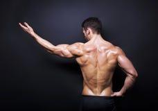 Muskulöse Mannesrückseite auf schwarzem Hintergrund Lizenzfreie Stockfotos