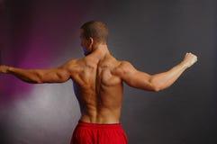 Muskulöse Mannesrückseite in den roten Kurzschlüssen Lizenzfreie Stockbilder