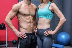 Muskulöse Paare mit den Händen auf den Hüften Stockbild