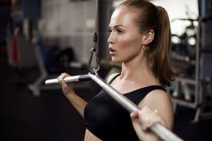Muskulöse Sitzfrau, die Gebäudemuskeln ausübt Stockbild