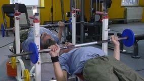 Muskulöser älterer Mann, der mit der Bank eindrückt die Turnhalle ausarbeitet Hebenübungen, zum stark und gesund zu sein stock footage