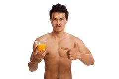 Muskulöser asiatischer Mannpunkt zum Orangensaft Lizenzfreies Stockfoto