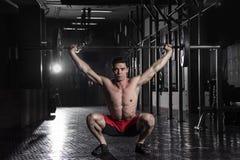 Muskulöser Athlet, der das crossfit exerise in der Turnhalle tut Handeln Stockfotografie
