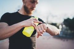 Muskulöser bärtiger Athlet, der gebrannte Kalorien auf elektronischer intelligenter Uhranwendung nach dem guten Training im Freie Lizenzfreie Stockbilder