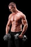 Muskulöser Bodybuilder, der mit zwei Gewichten trainiert Stockfotografie