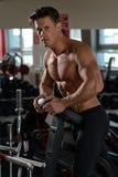 Muskulöser Bodybuilder, der sich vorbereitet, in der Turnhalle zu trainieren Lizenzfreie Stockfotos