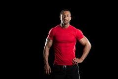 Muskulöser Bodybuilder-Mann, der über schwarzem Hintergrund aufwirft stockbild