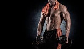 Muskulöser Bodybuilderkerl, der Übungen mit Dummköpfen über bla tut Lizenzfreie Stockfotos