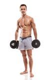Muskulöser Bodybuilderkerl, der Übungen mit Dummköpfen tut stockfotografie
