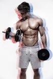 Muskulöser Bodybuilderkerl, der Übungen mit Dummköpfen tut lizenzfreies stockbild