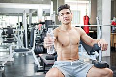 Muskulöser Bodybuilderkerl, der auf einer Bankshow-Wasserflasche a sitzt lizenzfreie stockfotos