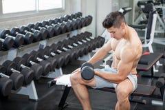 Muskulöser Bodybuilderkerl, der die Übungen sitzen mit Gewichthebendummköpfen in der Turnhalle tut Eignungs-Manntraining des hemd lizenzfreie stockbilder