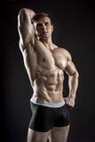 Muskulöser Bodybuilderkerl, der die Aufstellung über schwarzem Hintergrund tut Lizenzfreie Stockfotos