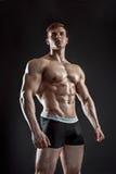 Muskulöser Bodybuilderkerl, der die Aufstellung über schwarzem Hintergrund tut Stockbild