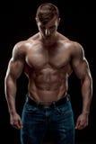 Muskulöser Bodybuilderkerl, der die Aufstellung über schwarzem Hintergrund tut Stockbilder