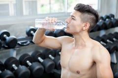 Muskulöser Bodybuilderkerl, der nachher auf einem Trinkwasser der Bank sitzt lizenzfreie stockfotografie