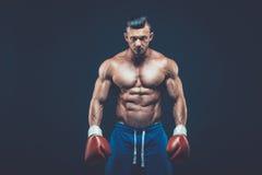 Muskulöser Boxer im Studioschießen, auf schwarzem Hintergrund Lizenzfreie Stockbilder