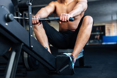 Muskulöser Eignungsmann, der Rudermaschine verwendet stockfotografie