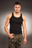 Muskulöser gutaussehender Mann im schwarzen Hemd- und Hosengelände Stockfotografie