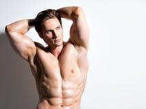 Muskulöser gutaussehender Mann mit den Händen hinter Kopf Lizenzfreies Stockfoto