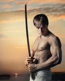 Muskulöser hübscher Kerl mit Klinge bei Sonnenuntergang stockfotos