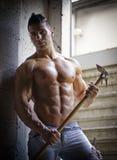 Muskulöser hemdloser junger Mann mit der Landwirtschaft des Werkzeugs Stockbild