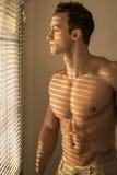 Muskulöser hemdloser Mann nahe bei Jalousien Stockfoto