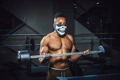 Muskulöser junger Afroamerikanermann in Maske anhebendem Barbell auf Bizeps Übung für Bizeps mit Barbell schwarzer Mann in der Tu Stockbild