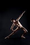 Muskulöser junger Athlet, der in das schwarze Studio ausdehnt stockbild
