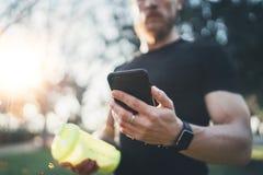 Muskulöser junger Athlet, der gebrannte Kalorien auf Smartphoneanwendung nach Sitzung des guten Trainings im Freien auf sonnigem  Stockbilder