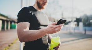 Muskulöser junger Athlet, der gebrannte Kalorien auf Smartphoneanwendung nach Sitzung des guten Trainings im Freien auf sonnigem  Stockbild